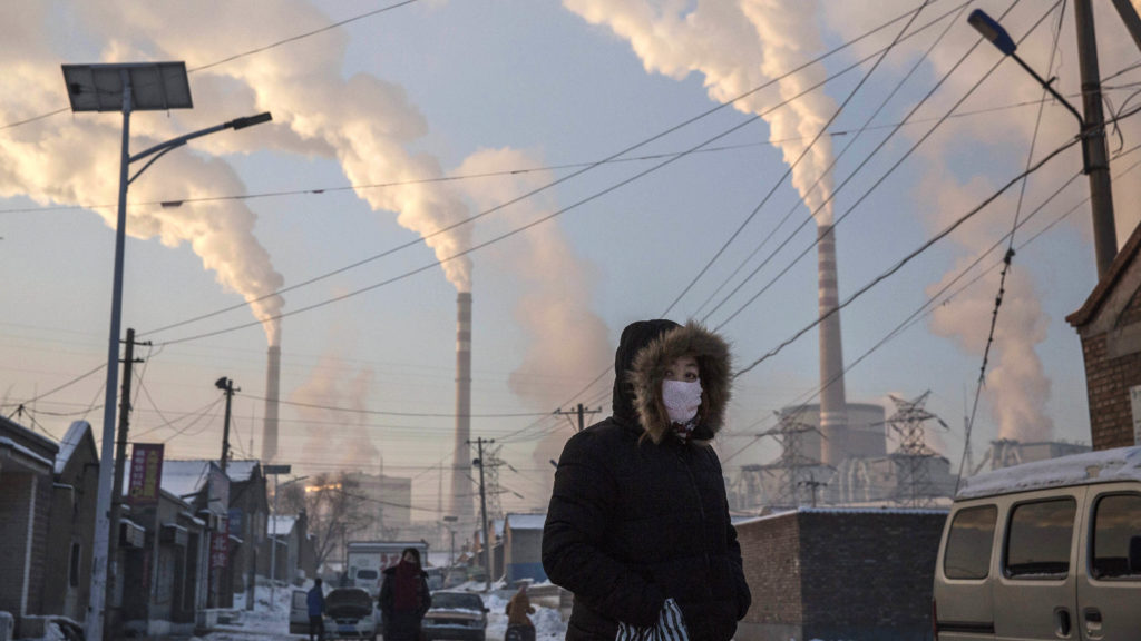KEVIN FRAYER/GETTY IMAGES Smoke billows from the stacks of coal-fired electricity plants as a woman wears a mask while walking in a neighborhood in Shanxi, China.
