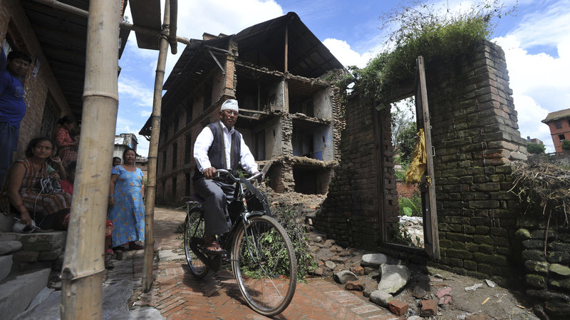 A bicyclist passes a home damaged in a 2011 earthquake at Bhaktapur, some 7 miles southeast of Kathmandu. Prakash Mathema /AFP/Getty Images