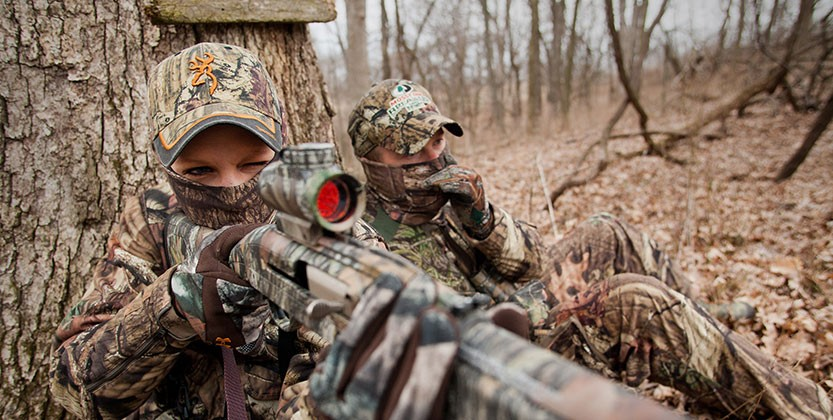 A hunter in camoflauge, sitting next to another hunger, takes aim with a firearm.