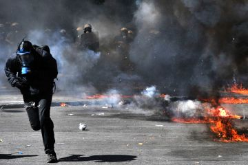A protester runs from police in Athens on Wednesday. (Louisa Gouliamaki/AFP/Getty Images)