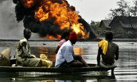 Niger delta residents pass a burning Shell oil pipeline as they evacuate their homes by boat in December 2005. (Photo: George Osodi/AP)